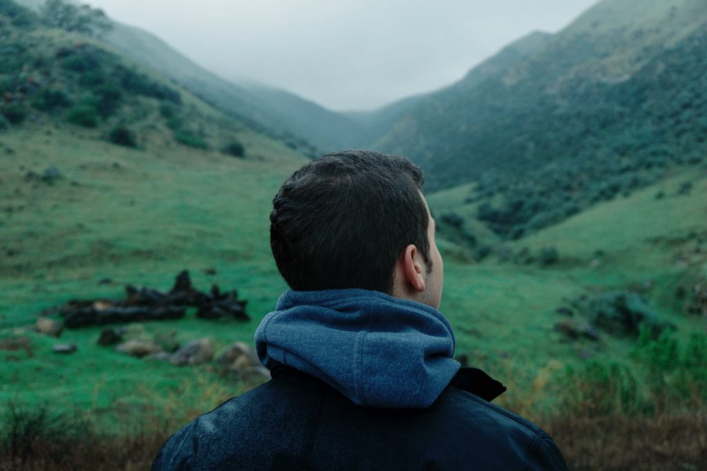 Man looking out over a field and mountains